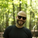 A portrait of David Romsey, Backend Engineer at WebDevStudios. David is outdoors wearing sunglasses and facing the camera and smiling.