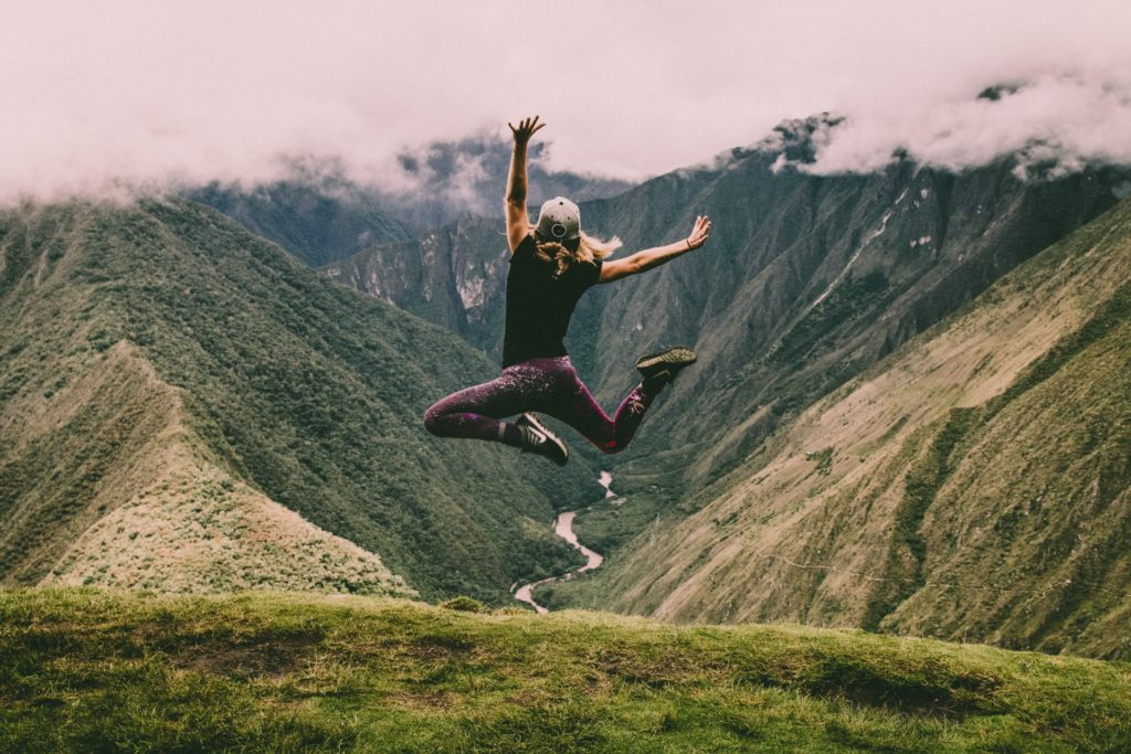 This is a photograph of a woman jumping with glee as she overlooks an Inca trail in Peru.