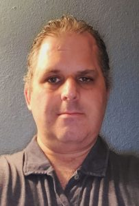 This is a selfie style photo of Robert Gillmore, Support Engineer at Maintainn, the WordPress maintenance and support division of WordPress agency, WebDevStudios. Robert is wearing a gray shirt and looking at the camera.
